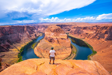 A young man in a white shirt and a green hat at Horseshoe Bend and the Colorado River in the background, Arizona. United States