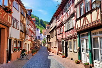Fototapete - Beautiful traditional half timbered buildings along a street in the town of Miltenberg, Bavaria, Germany