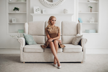 Gorgeous pretty lady sitting in luxury apartment and holding hands on knees. Beautiful young woman in elegant beige dress posing on white sofa. Happy blonde model relaxing after long working day. Wall mural