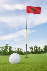 Morocco flag on golf course putting green with a ball near the hole