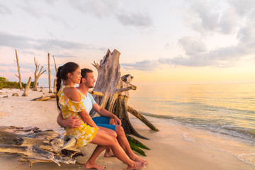Couple in love watching romantic sunset on Florida beach summer travel getaway destination, Lovers key beach in the Gulf of Mexico. Woman and man hugging relaxing. Southwest Florida.