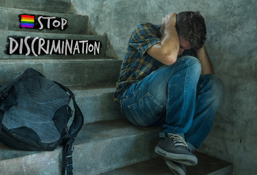 free sexual orientation and LGBT tolerance and respect campaign with young harassed and bullied homosexual student man sitting on staircase victim of bullying and abuse