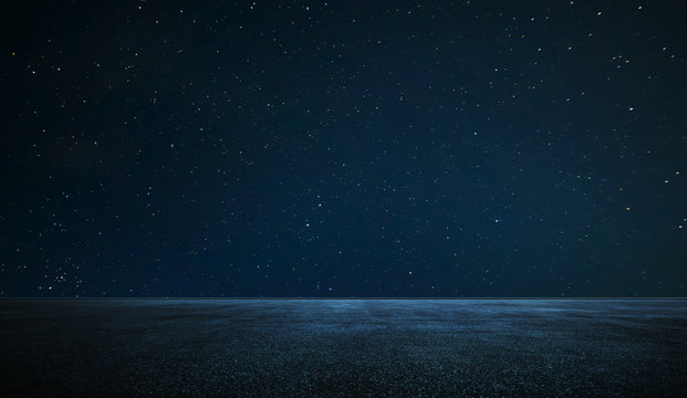 Empty asphalt floor with night sky .