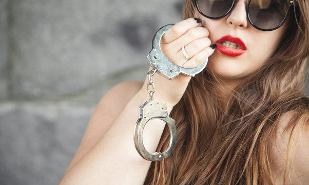 Sexy beautiful woman holding handcuffs.