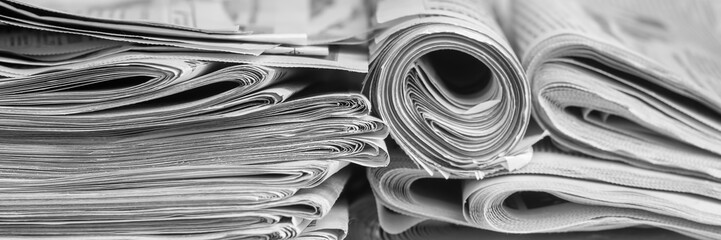A stack of folded newspapers on the desktop in the office. Latest financial and business news in daily paper.