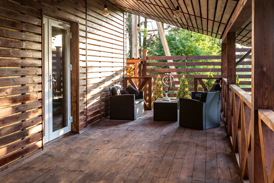 interior of empty hall veranda in wooden village vacation home with vintage lamps and chairs