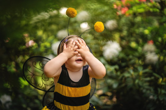 Baby girl in costume of bee covering her eyes with hands . Funny expression. Copy space