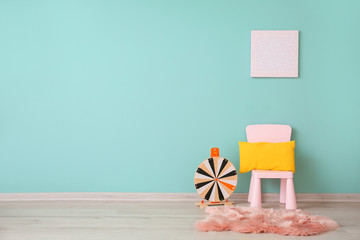 Chair with play wheel near color wall in children's room