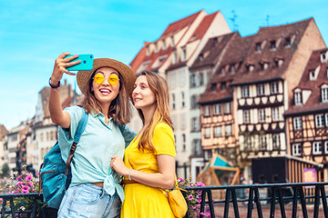 Two multicultural girl friends take a selfie on smartphone while traveling in European old cities. Vacation and relationship concept