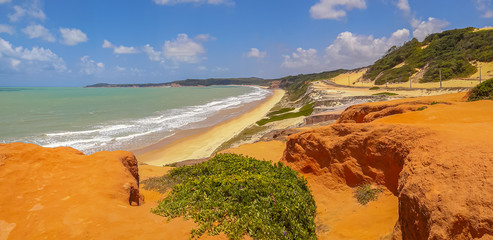 Panorama of brasilian beach with dunes bathed by ocean waves, Pipa, Natal, Brasil