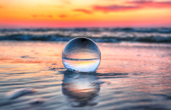 Beautiful sunset on the beach in Slowinski National Park near Leba, Poland. View through a glass, crystal ball (lensball) for refraction photography. Wild, untouched nature.