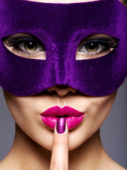 Portrait of a beautiful  woman with purple nails and violet theatre mask on face.
