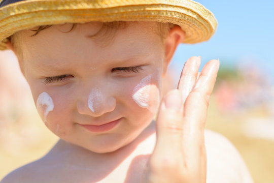 Mother puts cream on her son's face. Caring for baby skin. Sunscreens in the travel