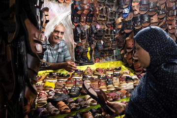 An Iranian woman buys shoes at a shoes store in a local bazaar at Bandar Abbas