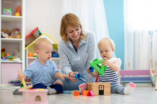 Teacher and one years old babies playing with educational toys in kindergarten