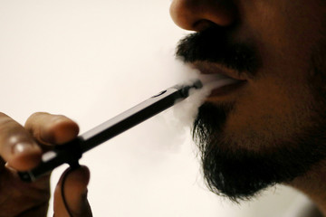 Ali Mansoor, an Emirati vape enthusiast, poses while smoking an e-cigarette at a cafe in Dubai
