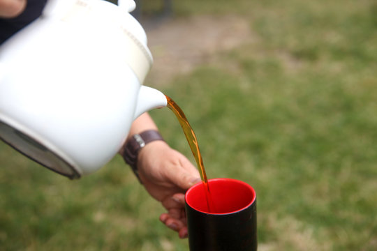 Woman pouring tea from the kettle into the cup