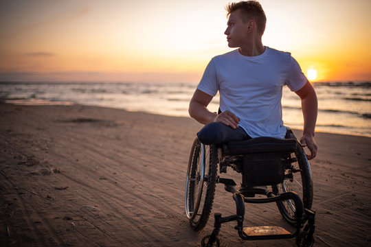 Handicapped man in wheelchair and his girlfriend alone on a beach at sunset