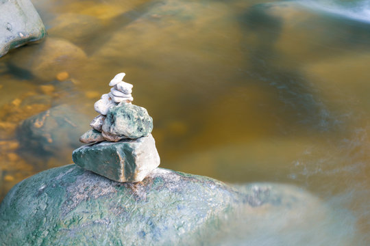 Stone tower resting near a flowing creek in autumn.