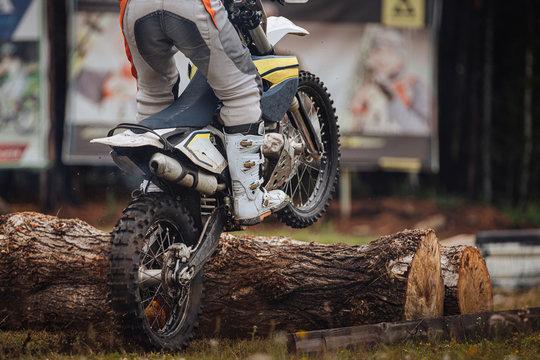 athlete racer motocross enduro riding pine logs in competition motocross