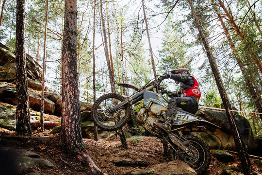 athlete racer motocross enduro riding uphill in forest trail