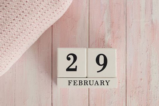 29 February Date on Cubes. Date on painted pink wood, next to baby blanket. Theme of baby due dates and birth dates.
