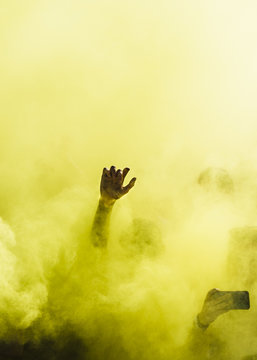 Close-up of people dancing and in yellow explosion of holi color