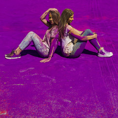 Tuinposter Feeën en elfen Young women sitting back to back over the purple holi color