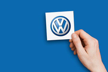 LONDON, UK - October 26th 2018: Hand holding an volkswagen logo. volkswagen is an automobile manufacturer.