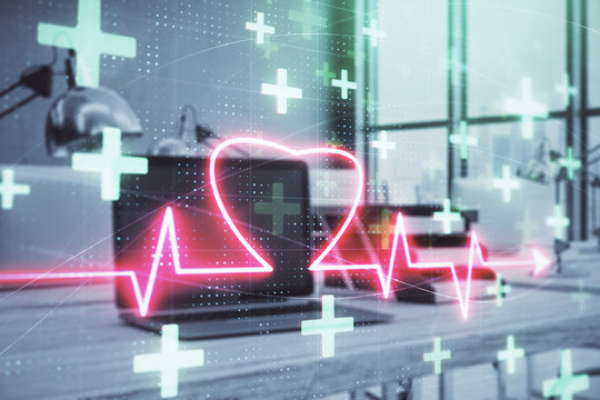 Heart hologram with desktop office background. Double exposure. Concept of medical education