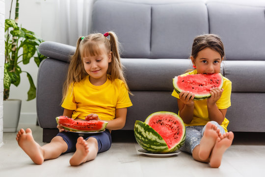 Child eating watermelon, two little girls eat watermelon at home