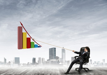 Man pulling with effort big pulling rope graph, as a symbol of financial growth
