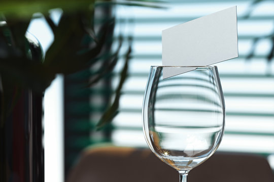 Wine glass with blank business card inside. restaurant is on background. 3d rendering.