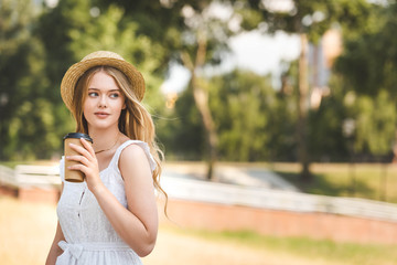 Wall Mural - beautiful girl in white dress and straw hat holding paper coffee cup and looking away