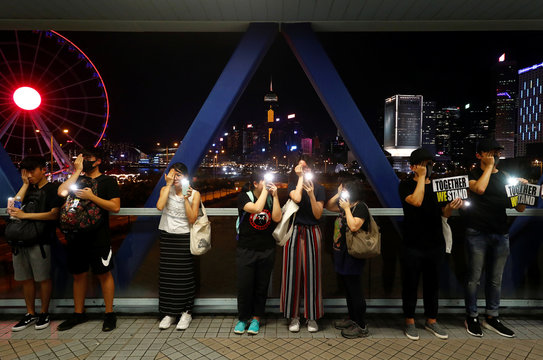 Protesters cover their right eye as they form a human chain during a rally to call for political reforms in Hong Kong's Central district