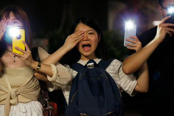 Protesters light up their smartphones and cover their right eye as they form a human chain during a rally to call for political reforms along Tsim Sha Tsui and Hung Hom Promenade in Hong Kong