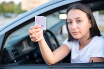Young woman holding driver license in her car