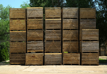 Pile of empty wooden crates at warehouse backyard on sunny day Wall mural