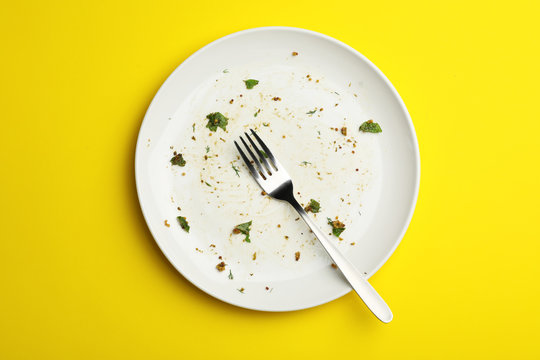 Dirty plate with food leftovers and fork on yellow background, top view