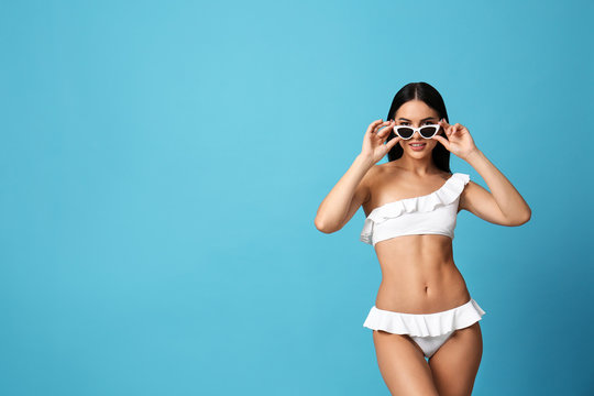 Beautiful young woman in white bikini with sunglasses on light blue background. Space for text
