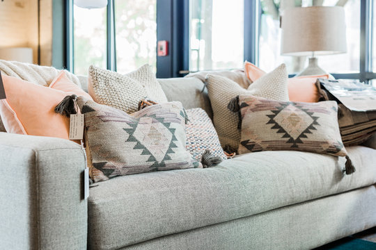 modern grey couch with pink and grey bohemian throw pillows