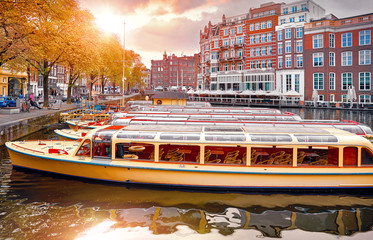 Fototapete - Amsterdam, Holland, Netherlands. Amstel river, canals and boats against evening dusk sunset sky cityscape. Pleasure boat for touristic tour.