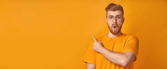 Surprised male hipster with trendy hairdo and red beard, keeps mouth opened, being stupefied as advertises something, wears yellow tshirt, indicates with fore finger at upper right corner. Omg concept
