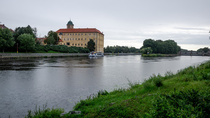 Castle by the river during the light shower in Podebrady town