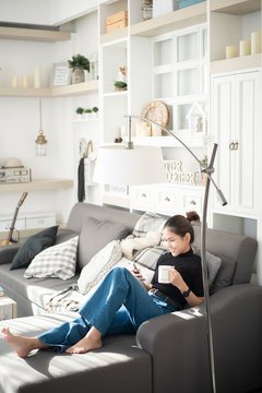 Young beautiful woman relaxing on sofa at home and using smart phone
