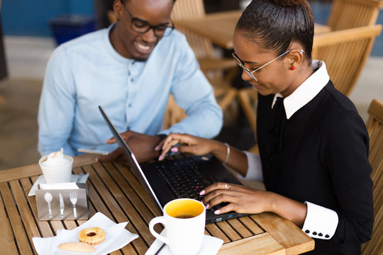 Black  African American coworkers doing digital teamwork arround a coffee cup