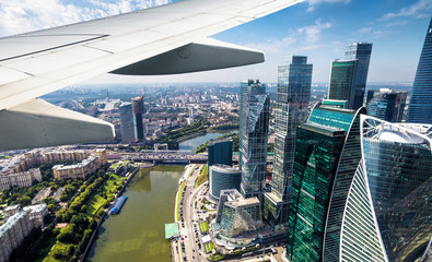 Wall Mural - Plane flies above Moscow, Russia. Aerial panoramic view of Moscow-City from airplane window. The plane's wing over modern Moscow skyscrapers. Concept of flight, vacation and summer travel.