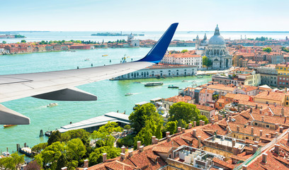 Fototapete - Plane flies above Venice, Italy. Aerial panoramic view of city and sea from airplane window. The plane's wing over Venice during taking off or landing. Concept of flight, vacation and summer travel.