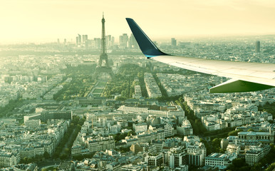 Fototapete - Plane flies above Paris, France. Aerial panoramic view of Eiffel tower from airplane window. The plane's wing over streets of Paris. Concept of air travel to Paris. Flight in Europe in summer.