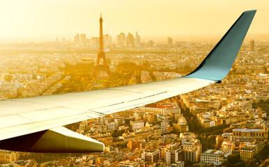 Wall Mural - Plane flies above Paris in summer evening, France. Aerial panoramic view of Eiffel tower from airplane window. The plane's wing over streets of Paris at sunset. Flight and air travel to Paris.